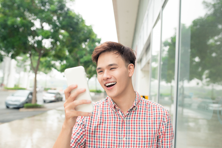 Vrolijke knappe man die iets op mobiele telefoon controleren Stockfoto