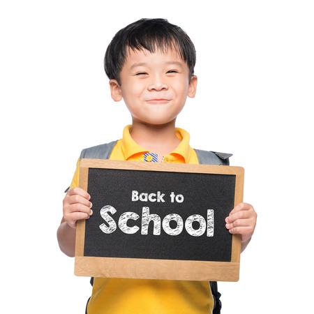 Jonge Aziatische jongen glimlach die terug naar het schoolbord over wit houdt