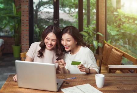 Felices relajados jóvenes amigas haciendo compras en línea a través de la computadora portátil y la tarjeta de crédito en casa