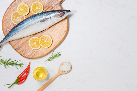 spice: Fish dish cooking with various ingredients. Fresh raw fish decorated with lemon slices and herbs on wooden table.