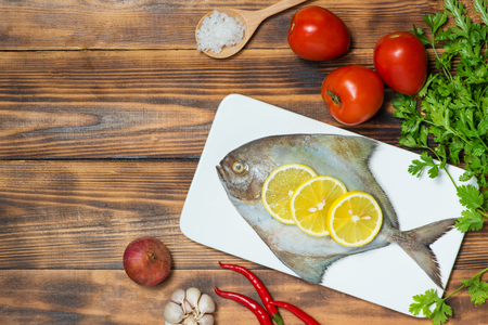 Fish dish cooking with various ingredients. Fresh raw fish decorated with lemon slices and herbs on wooden table.
