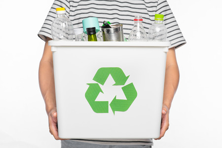Eco concept. Male hands holding recycling bin full of recyclable items isolated on a white background. Stock Photo