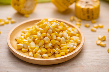Sweet corn seeds on a wooden plate