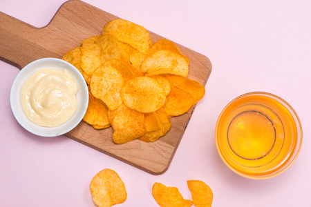 Cheese and onion potato chips with soft drink on pink background.