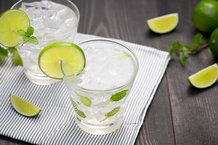 Verse cocktail met limoen, ijs en munt op een rustieke achtergrond. Kopieer ruimte, bovenaanzicht