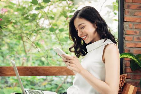 Zuversichtlich junge asiatische Frau in der intelligenten Freizeitkleidung , die am Telefon schreibt
