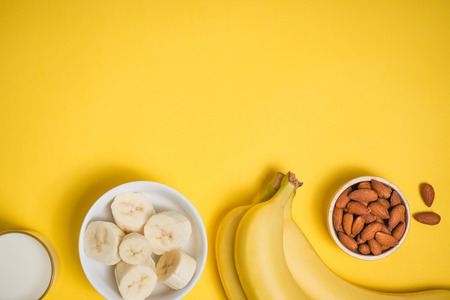 A banch of bananas and a sliced banana in a dish over yellow background. Zdjęcie Seryjne - 82813972