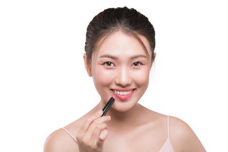 Beautiful young asian woman applying pink lipstick