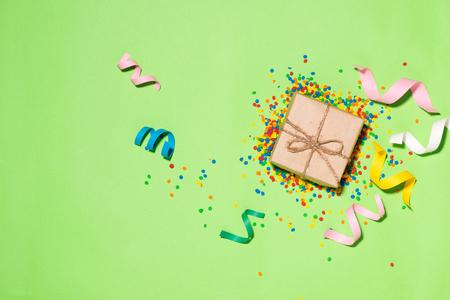 Viering Flat lay. Cadeau doos met kleurrijke feestartikelen op groene achtergrond.