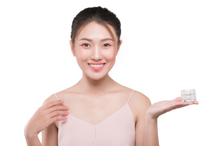 Attractive girl with soft skin and naked shoulders holding cream, a model with light nude make-up