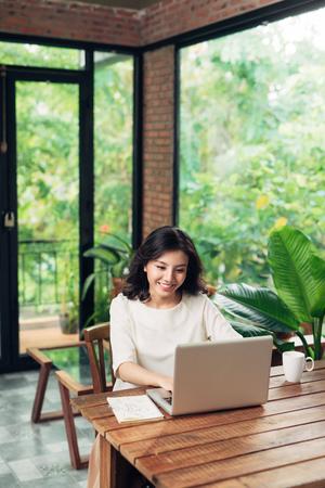 作業自宅でラップトップを使用して若い女性の肖像画。 写真素材
