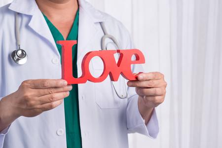 Asiatischer männlicher Doktor mit dem Stethoskop, das Liebesbriefe, lokalisiert auf weißem Hintergrund hält Standard-Bild - 82814047