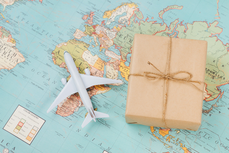 International shipping. White model airplane land on the geographical map background Archivio Fotografico