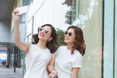Twee jonge meisjes gaan samen winkelen en nemen selfiefoto door mobiele telefoon