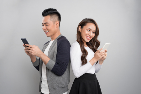 Beautiful young asian couple holding mobile phones and standing back to back against grey background