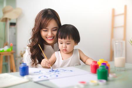 Glückliche Familie Mutter und Tochter zusammen malen. Asiatische Frau hilft ihrem Kind Mädchen. Standard-Bild - 83058836