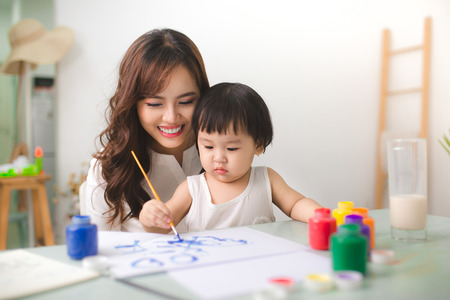 Happy family mother and daughter together paint. Asian woman helps her child girl. Imagens