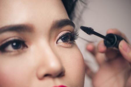 Close-up portret van mooi meisje aan het raken van zwarte mascara aan haar wimpers Stockfoto