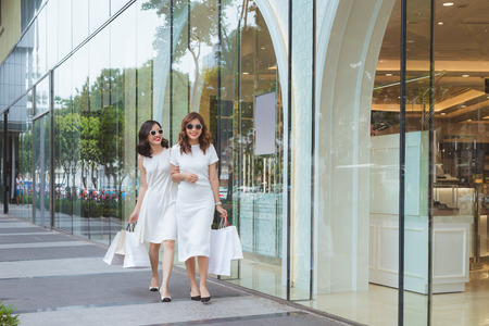 Young beautiful happy women with shopping bags on street at the mall