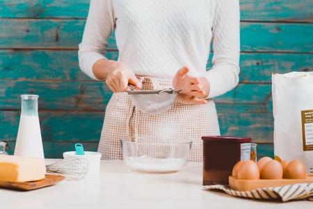 L'épouse de la maison porte le tablier. Étapes de fabrication de gâteau au chocolat. Banque d'images - 82905172