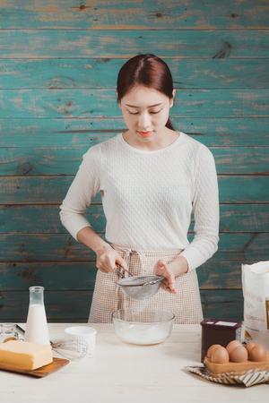 L'épouse de la maison porte le tablier. Étapes de fabrication de gâteau au chocolat. Banque d'images - 83701669