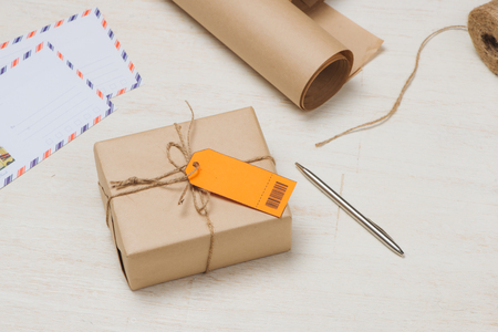 Parcel tied with string with address orange label attached Foto de archivo