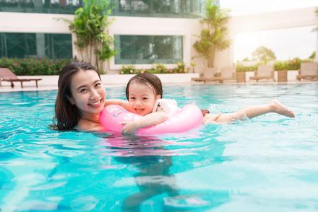 Moeder en baby meisje met plezier in het zwembad. Zomervakantie en vakantie concept