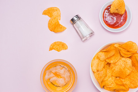 Concept of unhealthy food. Potato chips in a bowl and ketchup