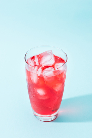 Soda. Red sparkling water with ice in a glass