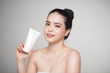 Beauty concept. Asian pretty woman with perfect skin holding cosmetic bottle