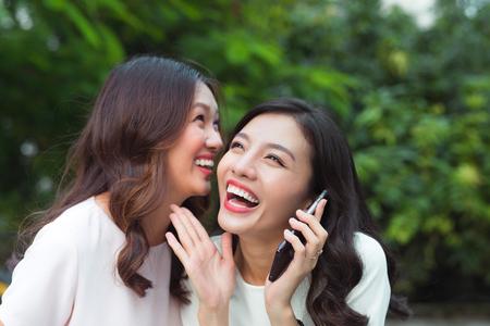 Junge asiatische Frau, die Geheimnis in ein Freundohr flüstert, während shes auf Anruf Standard-Bild