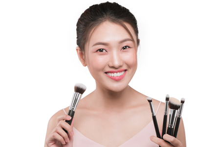Portrait of attractive young asian woman holding make-up brushs over white Фото со стока - 83163748