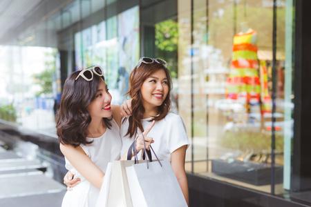 Twee mooie meisjes venster winkelen in de stad Stockfoto