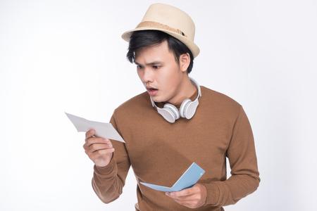 Mâle asiatique touristique tenant passeport sur fond gris Banque d'images - 83242155
