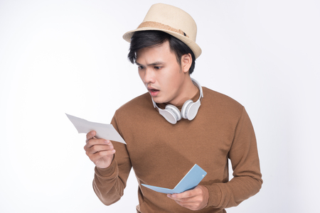 Worried asian male tourist holding passport over grey background