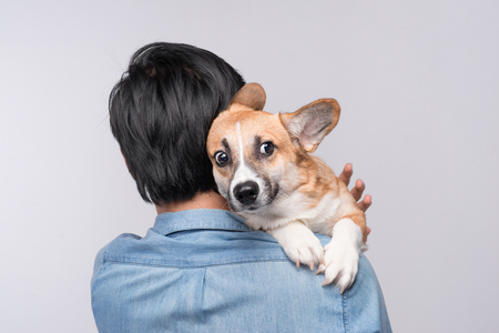 A man snuggling and hugging his dog, close friendship loving in studio background Stok Fotoğraf - 83242156