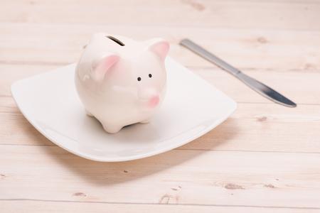 Een roze spaarvarken op de schotel. Financieel concept. Stockfoto