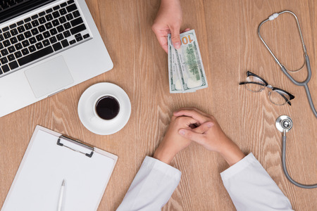 Cropped image of young doctor in white coat talking money from his patient while working in office Stock Photo