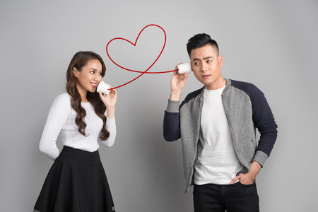 Young asian couple with can phone isolated on gray background Banco de Imagens