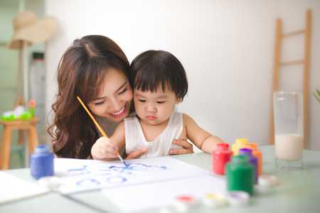 Happy family mother and daughter together paint. Asian woman helps her child girl. Фото со стока