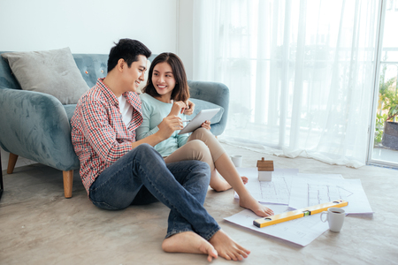Attractive young asian adult couple looking at house plans. Banco de Imagens