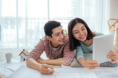 Attractive young asian adult couple looking at house plans. Imagens