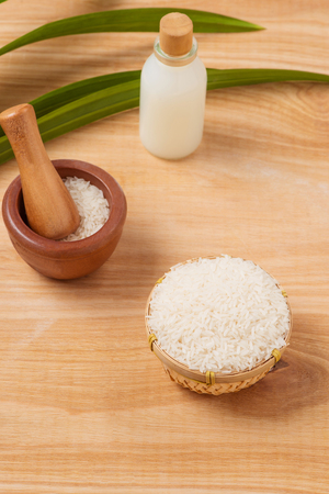 Rice flour in a wooden bowl, milk and rice on the old wooden background