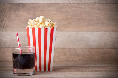Popcorn in rood en wit karton met frisdrank op houten lijst.