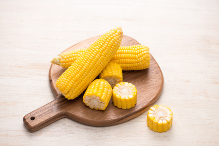 Sweet corn on cobs on cutting board on wooden table.