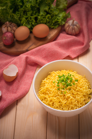 Instant noodles in bowl with vegetables on wood background Stock Photo