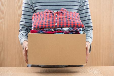 남성 손에 의류 가난한 사람들을위한 기부 상자