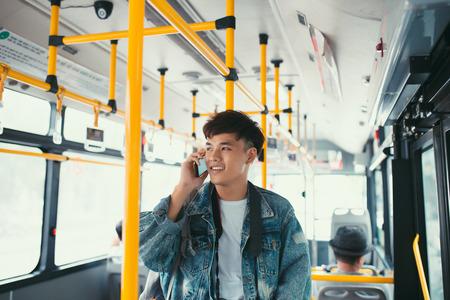 Knappe Aziatische mens die zich in stadsbus bevindt en op mobiele telefoon spreekt Stockfoto