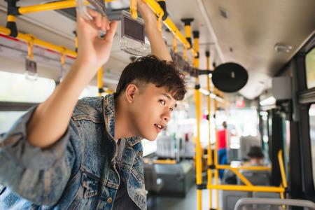 公共交通機関、バスの中に立っている男性。 写真素材
