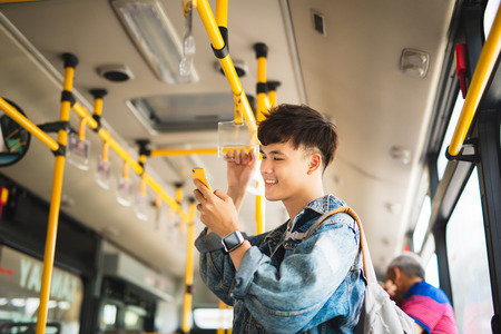 Asian man taking public transport, standing inside bus.